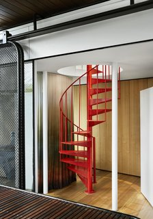 A red metal spiral staircase leads to the second-story office.