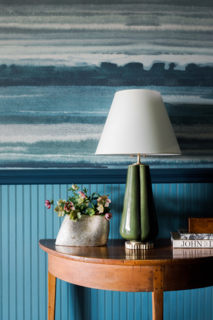 In the foyer, Phillip Jeffries' tranquil blue Fade Sea Spray wallpaper gives a subtle nod to the nearby Blue Ridge Mountains, which guests have views of from the property.
