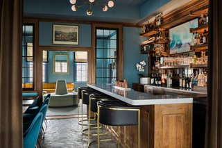 The most hands-on part of the inn's facelift happened in the bar and adjacent lounge area, where the front desk was removed and the bar was elongated. A new bar-back was constructed out of wood shelving and supported by copper piping.