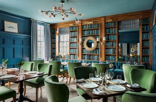 The Library, which serves as a dining room at the inn, was given a bold color scheme. The walls and paneling were painted in Farrow & Ball's Stiffkey Blue, and the ceiling was given a lighter shade. The Dallas Chandelier from Arteriors adds a sleek, contemporary edge to the space.