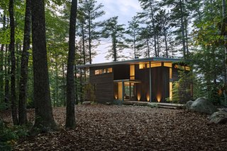 "Cedar siding is stained in dark brown to camouflage the cabin with the surrounding forest. ""It was important that this house appears modern and blends in,"" says Murdough."