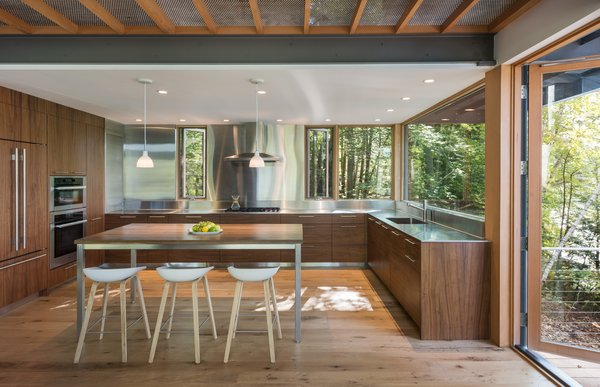 """In the kitchen, custom walnut cabinets are paired with stainless-steel countertops and backsplash to help reflect the natural setting. """"It captures the coloration of the landscape and the light, which makes it feel larger than it is,"""" says Murdough. """"Also, stainless steel is good for kitchens and work environments."""""""