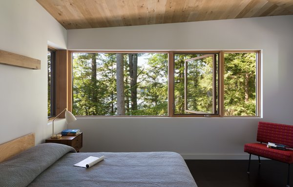 Above the bed, a custom wood valence acts as an indirect source of light that washes the wall in an ambient glow.