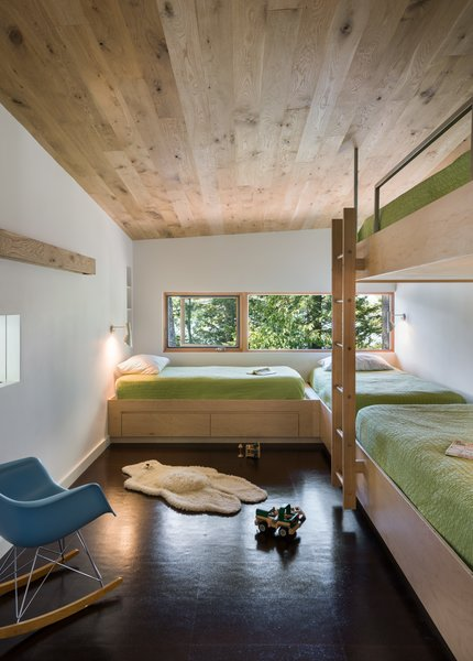 Custom, built-in bunk beds were constructed out of Baltic birch plywood, which stand out against the dark cork floors. Each bed includes a sconce for reading, along with built-in storage. In the bunk room, a sliding partition that opens to the adjacent catwalk adds a sense of whimsy.