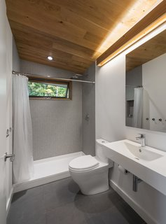 A clean, minimalist, spa-like bathroom is warmed up with a white oak ceiling and complementary lighting valence.