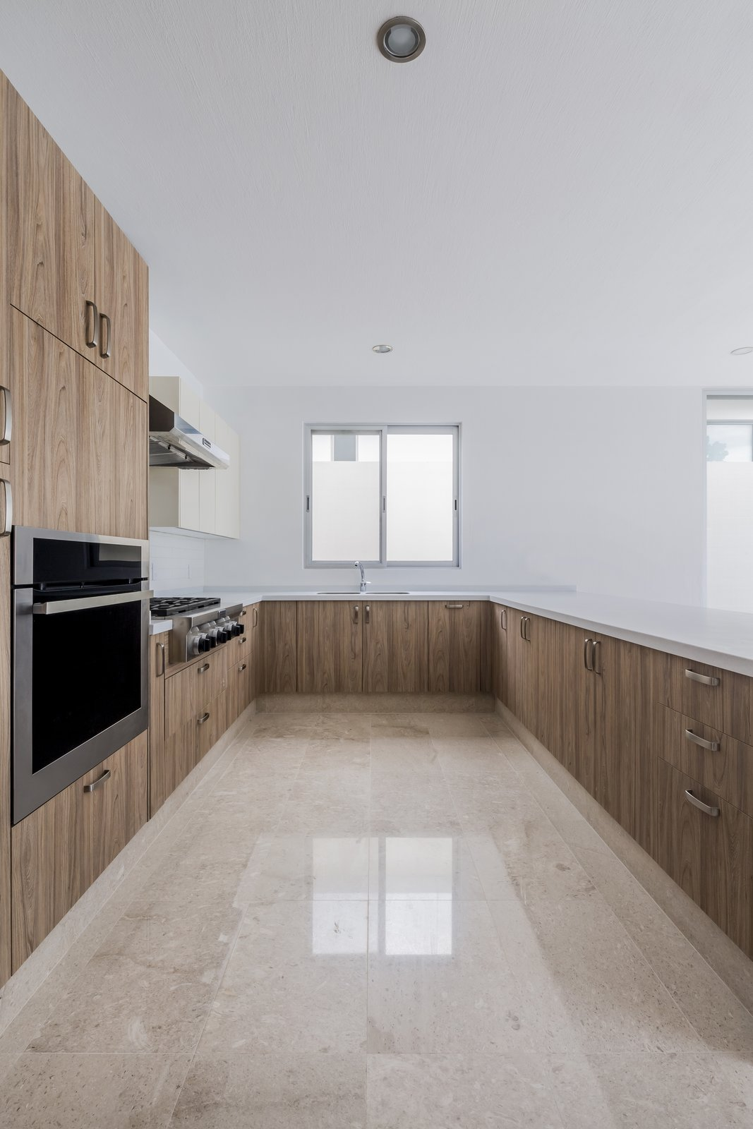 Kitchen, Wood Cabinet, Wood Counter, Marble Floor, Quartzite Counter, Ceramic Tile Backsplashe, Ceiling Lighting, and Wall Oven  CASA VALLE by Sergio Villalobos