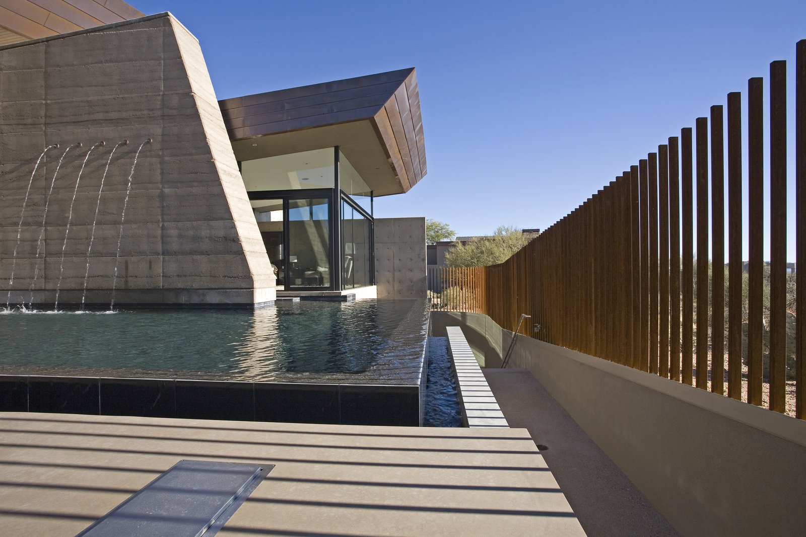 Outdoor, Trees, Desert, Hardscapes, Large Pools, Tubs, Shower, Back Yard, Infinity Pools, Tubs, Shower, Concrete Pools, Tubs, Shower, Swimming Pools, Tubs, Shower, Large Patio, Porch, Deck, Walkways, Concrete Patio, Porch, Deck, Vertical Fences, Wall, and Metal Fences, Wall  Desert Wing