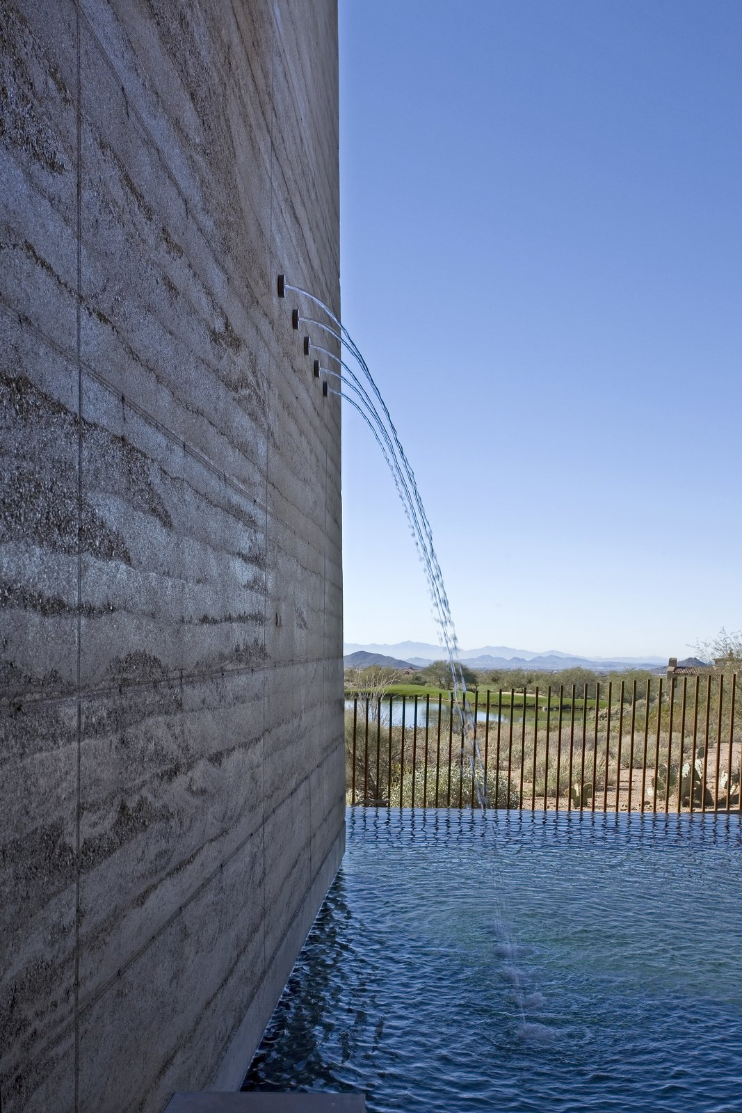 Outdoor, Trees, Shrubs, Back Yard, Desert, Grass, Large Pools, Tubs, Shower, Swimming Pools, Tubs, Shower, Infinity Pools, Tubs, Shower, Hardscapes, Concrete Pools, Tubs, Shower, Vertical Fences, Wall, and Metal Fences, Wall  Desert Wing