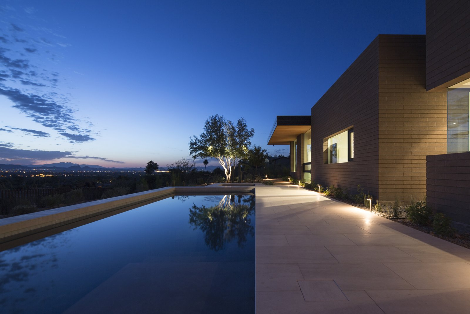 Outdoor, Back Yard, Shrubs, Trees, Hardscapes, Small Pools, Tubs, Shower, Concrete Pools, Tubs, Shower, Salt Water Pools, Tubs, Shower, Stone Patio, Porch, Deck, Large Patio, Porch, Deck, and Landscape Lighting  Rammed Earth Modern