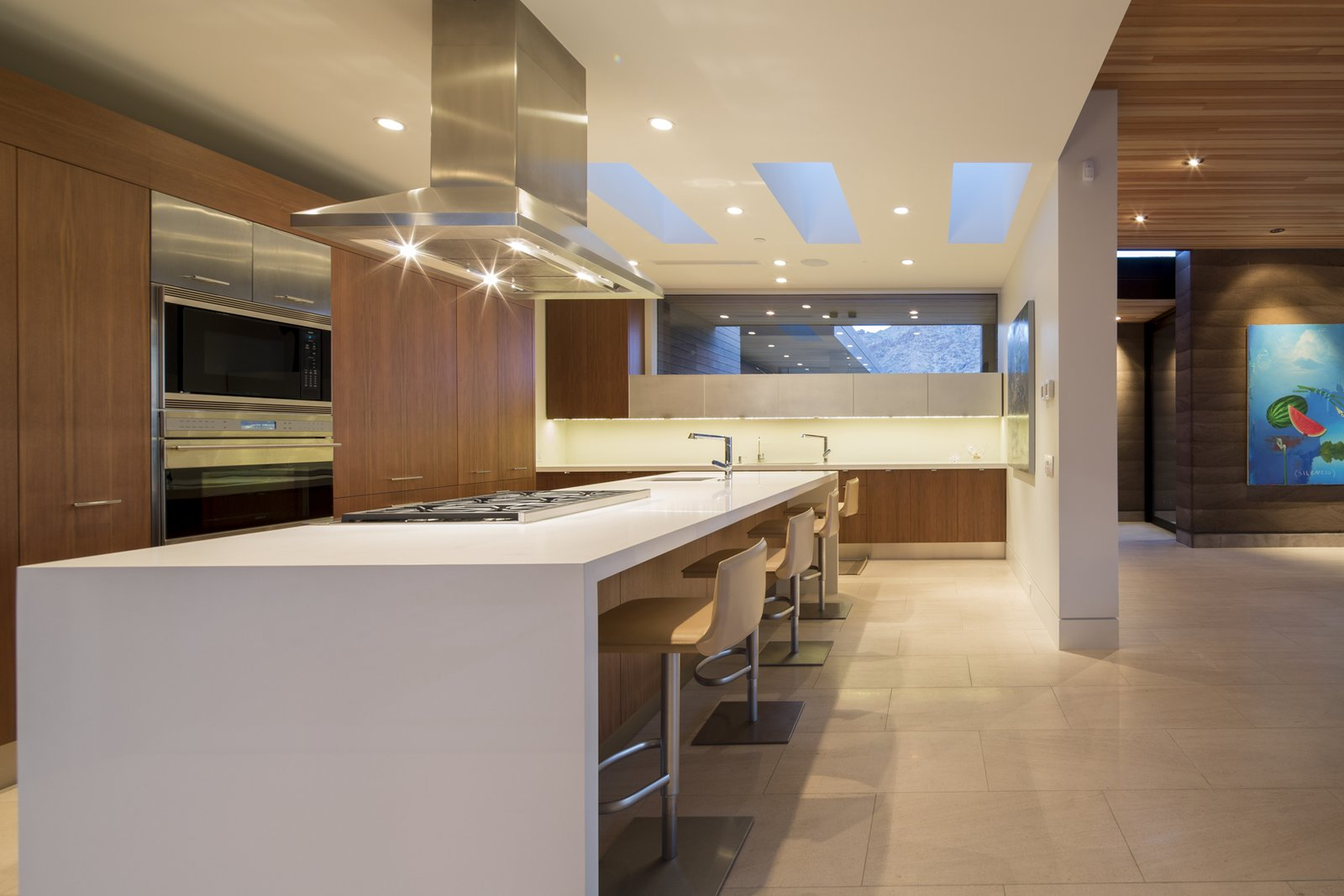 Kitchen, Quartzite Counter, Limestone Floor, Stone Slab Backsplashe, Recessed Lighting, Wood Cabinet, Refrigerator, Wall Oven, Microwave, Cooktops, and Undermount Sink  Rammed Earth Modern