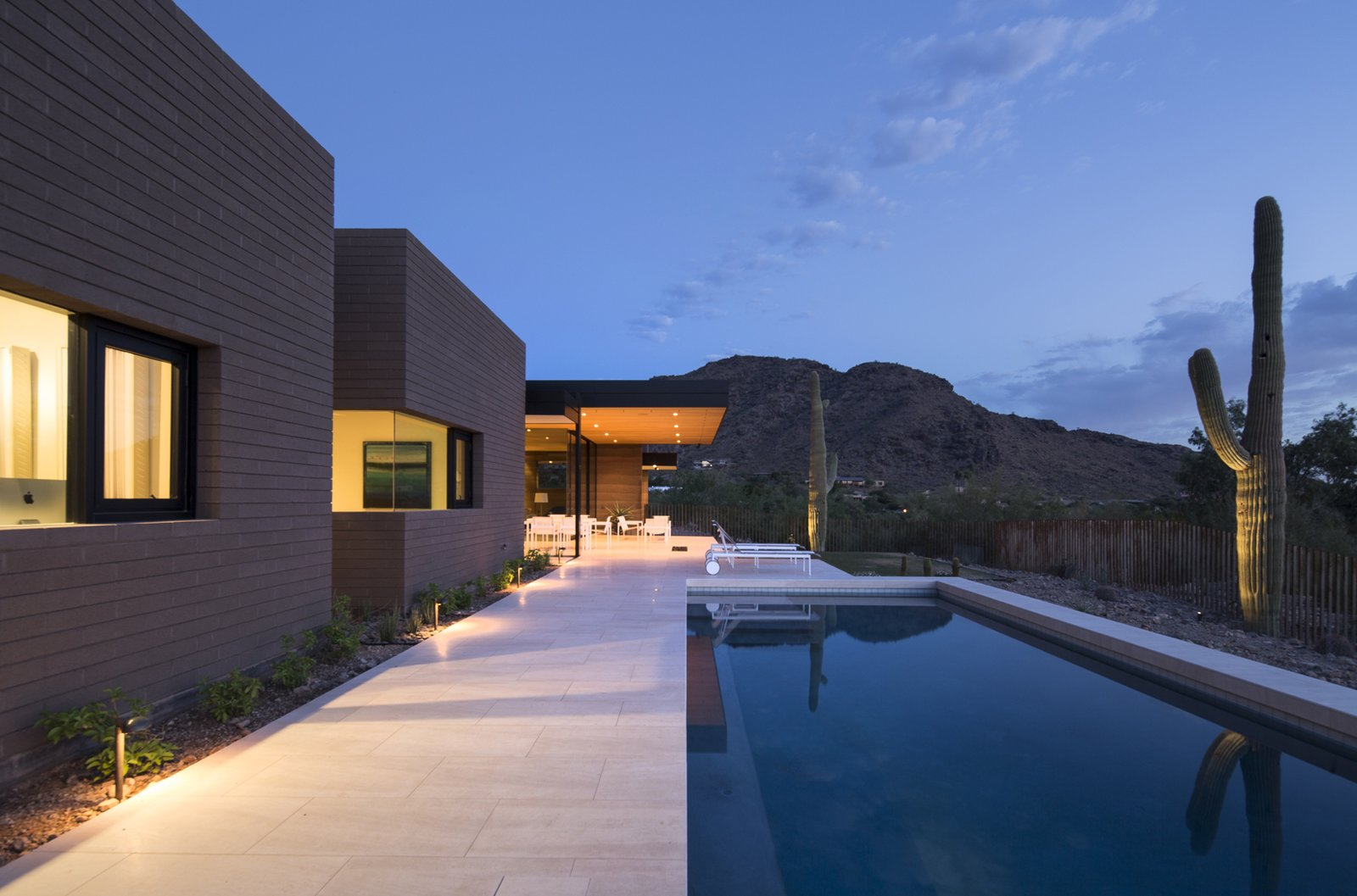 Outdoor, Back Yard, Trees, Concrete Pools, Tubs, Shower, Small Pools, Tubs, Shower, Grass, Hardscapes, Shrubs, Large Patio, Porch, Deck, Vertical Fences, Wall, Metal Fences, Wall, Landscape Lighting, and Stone Patio, Porch, Deck  Rammed Earth Modern