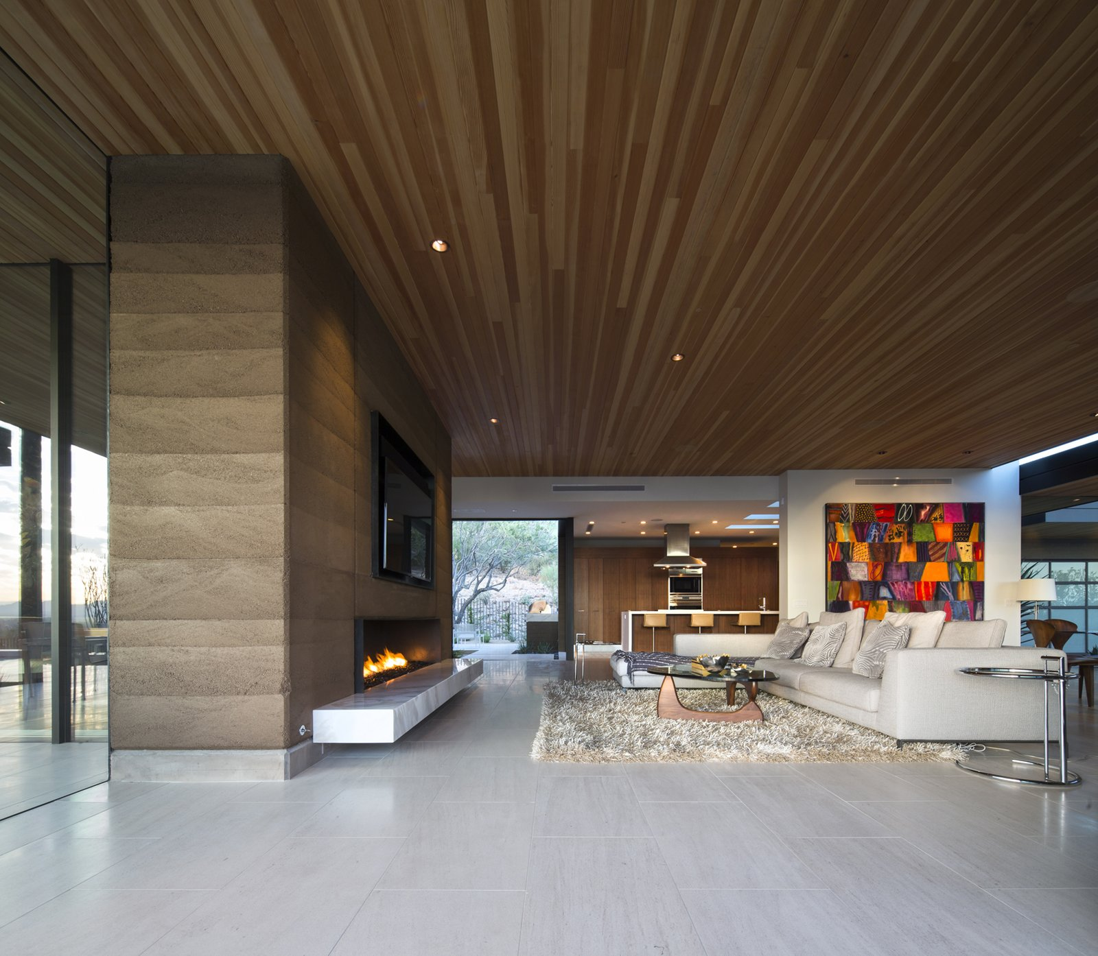 Living Room, Chair, Sofa, Sectional, Coffee Tables, Limestone Floor, Floor Lighting, Standard Layout Fireplace, End Tables, Recessed Lighting, Ribbon Fireplace, and Gas Burning Fireplace  Rammed Earth Modern