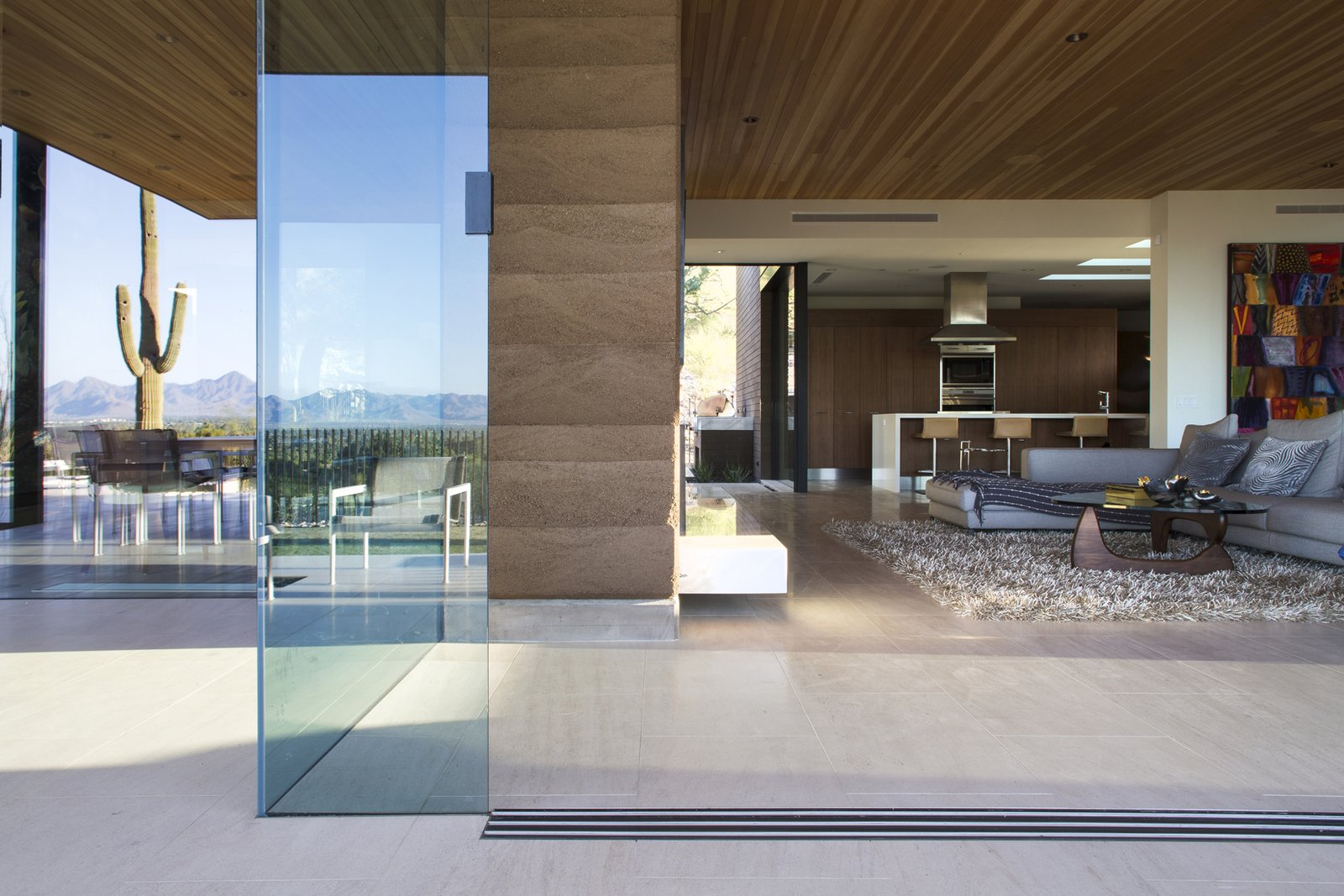 Living Room, Recessed Lighting, Sofa, Coffee Tables, Sectional, and Limestone Floor  Rammed Earth Modern