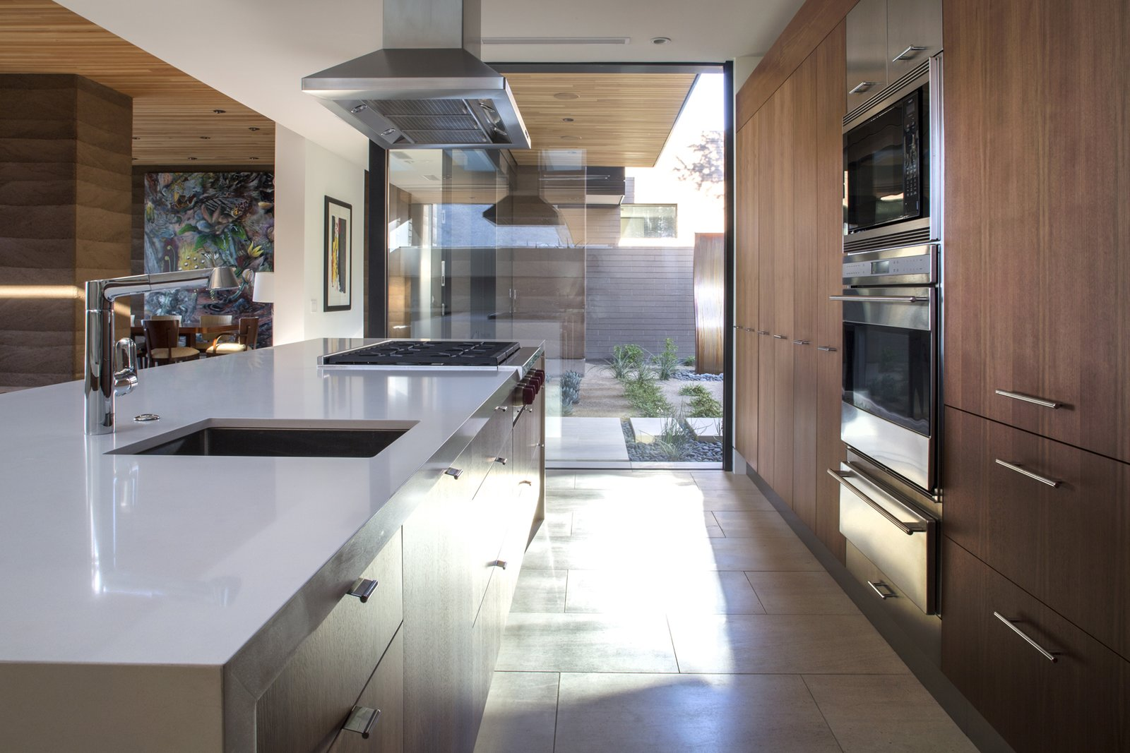 Kitchen, Limestone Floor, Wood Cabinet, Quartzite Counter, Recessed Lighting, Refrigerator, Wall Oven, Microwave, Cooktops, Range Hood, and Undermount Sink  Rammed Earth Modern