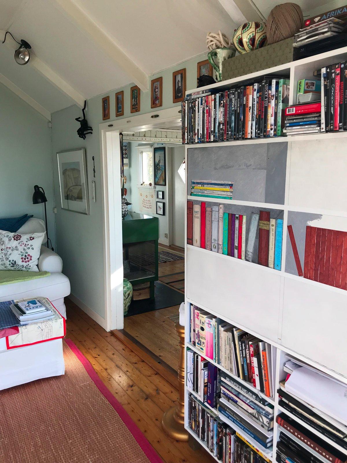 Living Room, Pendant Lighting, Ceiling Lighting, Light Hardwood Floor, Bookcase, and Wood Burning Fireplace  Paradiso