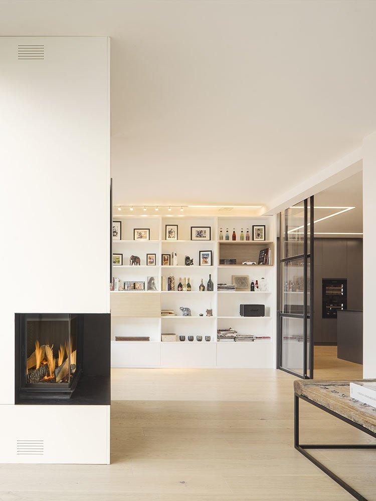 Living Room, Two-Sided Fireplace, Medium Hardwood Floor, Wall Lighting, and Bookcase  Black to Light by Susanna Cots