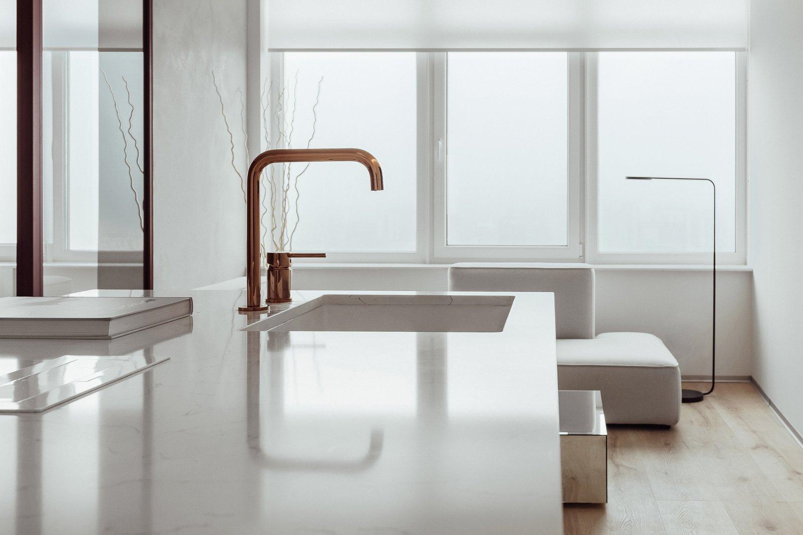 Kitchen, Quartzite Counter, Light Hardwood Floor, and White Cabinet  191 Apt.