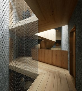 A wooden staircase contrasts with bare, concrete walls in Pilestredet P77.