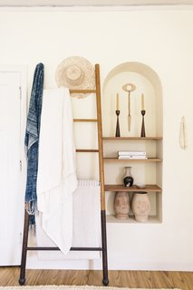 One of Zee's favorite nooks in the apartment, this alcove holds many of her treasured pieces, including the eye wall hanging by Heather Levine Ceramics.