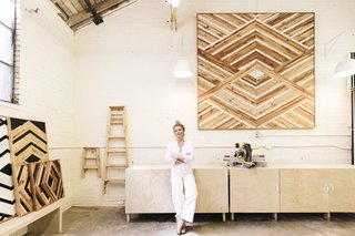 Zee proudly stands in front of her new large-scale piece in her Oakland workspace.