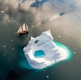 Sailboat creeping along the edge of an iceberg in Greenlands Sermilik Fjord.