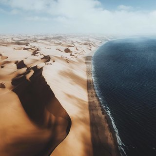 Flying high over the Namibian coast where thundering waves of the sea meet the rippling dunes of the desert Sandwich Harbour.