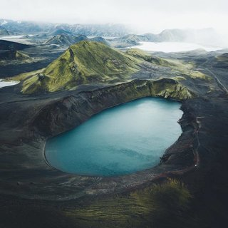 A massive crater lake in Iceland—see the tiny white car for scale.