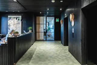Textured black surfaces and exposed concrete pay homage to San Francisco's iconic Transamerica Pyramid, while Raw Edges for Mutina tiles break up the harsh lines with a muted color pop.