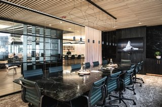Custom-designed conference tables made of blackened ash and Verde Alpi green-and-black marble offer a dramatic space to brainstorm and collaborate.