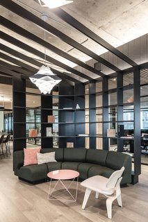 A literal canopy wraps around the the lounge serving as a shelf and barrier between the conference and work areas.