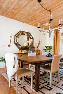 Young took cues from the home's architecture to refine the space while filling it with fresh decor. The floors are brick laid in sand, while large plank wood ceilings lie overhead. Adding to the neutral palette, the dining room is teeming with textures.