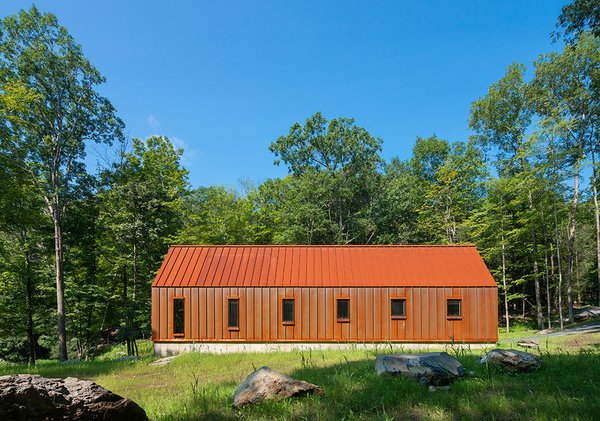 The Pond House has a standing-seam roof and wall panels made of Cor-Ten steel that throw the forest around it into relief.