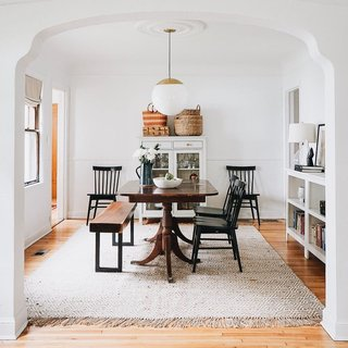 "This dining room plays many roles, serving as a place for meals, crafts, mail collection, reading, and a toy/human race track. Renovator Erin Francois says ""Cheers to small, multitasking homes that are typically never this clean."" Here she melds high and low with a Schoolhouse Luna pendant in black and Windsor dining chairs from Target."