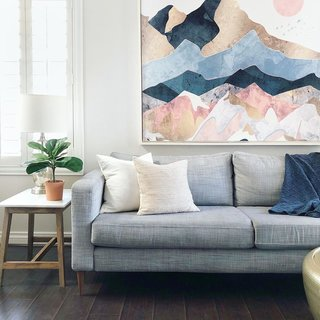 Rose kept the living room airy with an IKEA sofa with updated legs and a hanging wall tapestry.
