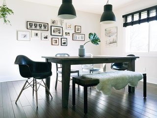 Reminiscent of Diane Keaton's inky abode, Conklin's moody dining room is furnished with Herman Miller chairs, IKEA pendant lights, and a Target bench.