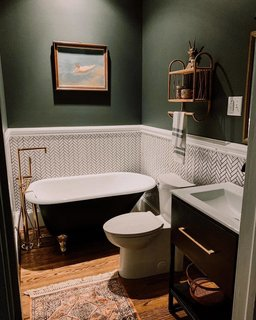 In this bathroom, the couple installed new flooring, swapped the shower stall for a tub, put in a new vanity, and updated the walls with tile and paint.