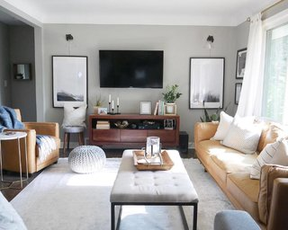 The living room features contemporary furnishings including a Babette brown leather and steel frame ottoman by Christopher Knight Home from Overstock, a Penelope round tufted accent stool from All Modern, a faux marble and gold end table from Pier 1, and a knitted silver-grey pouf from CB2.
