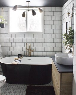 Two types of tile provide geometric texture against the inky soaking tub.