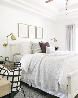 "The bedroom is airy but cozy. Wrinkly sheets are a ""problem"" that Hartley gives ""zero care units"" about. Adding a pop of color is a plum-hued pillow from Motif Pillows on Etsy."