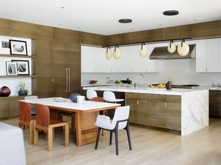 A generously sized chef's kitchen fits seamlessly with the contemporary lines of the home. A Rich Brilliant Willing Gala light is suspended above a Pietra Fina island. The backsplash features Heath Diamond tiles in Chalk-2. The dining table comprises a McGuire Furniture Company walnut base with a Staron top, and is surrounded by vintage Cassina and Poliform Ventura chairs.