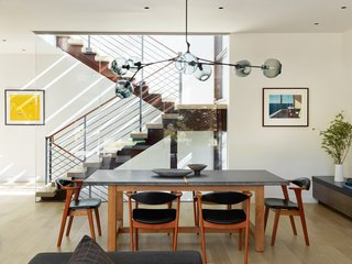 The formal dining area pairs a custom table by Heerenhuis Manufactuur with vintage Danish midcentury chairs. A Branching Chandelier by Lindsey Adelman in oil rubbed bronze with gray, glass globes hangs above the scene.