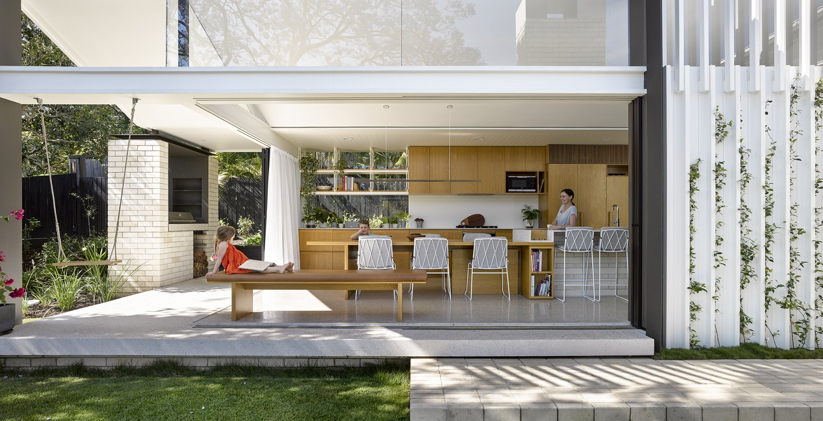 Kitchen, Ceiling Lighting, Microwave, Dishwasher, Limestone Floor, Drop In Sink, Wood Cabinet, Stone Slab Backsplashe, and Marble Counter  Photo 1 of 12 in An Architect Opens a 1920s Queenslander to the Great Outdoors