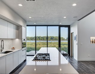 Although the front of the house has a neatly manicured lawn, the rear of the house looks out to views of the untamed prairie. The kitchen and its floor-to-ceiling glass doors were specifically designed to allow for views from the kitchen island out to the Missouri River.
