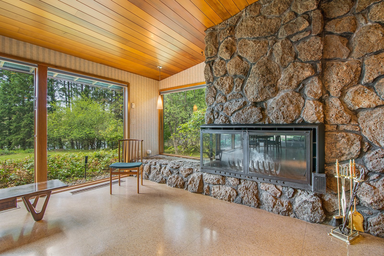 Living Room, Corner Fireplace, and Terrazzo Floor  Photo 11 of 11 in A Waterfront Washington Home Designed by a Renowned Spokane Architect Is Listed For $675K
