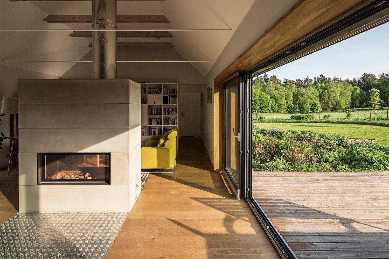 Living Room, Two-Sided Fireplace, Wood Burning Fireplace, Medium Hardwood Floor, and Ceiling Lighting  Nowa Górka by Studio GAB