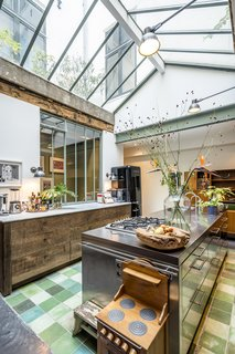 On a sought after an idyllic island in the center of Amsterdam an old warehouse, formerly in use as a pillow factory and a garage has been converted to a warm and eclectic family home. The kitchen features a mixture of green tiles, green painted mullions, and exposed wood beams for a warm, soft feeling that contrast sharply with the more industrial stainless steel island. The kitchen island incorporates a stove top and storage, and benefits from natural light from the skylight overhead.