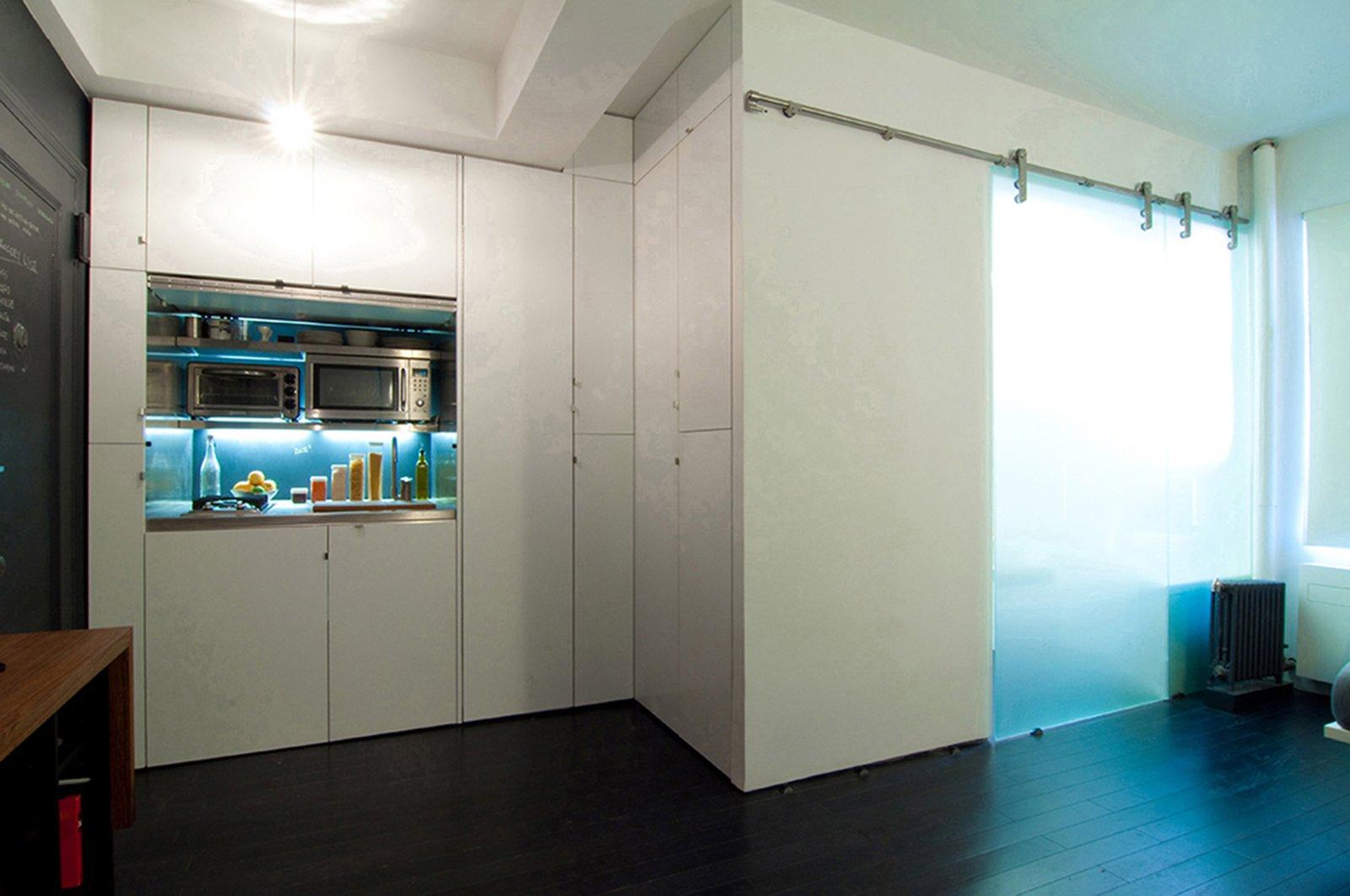 Kitchen, White Cabinet, Bamboo Floor, Ceiling Lighting, Metal Backsplashe, Microwave, Range, Metal Counter, Cooktops, Undermount Sink, Refrigerator, and Pendant Lighting  Park Avenue Studio