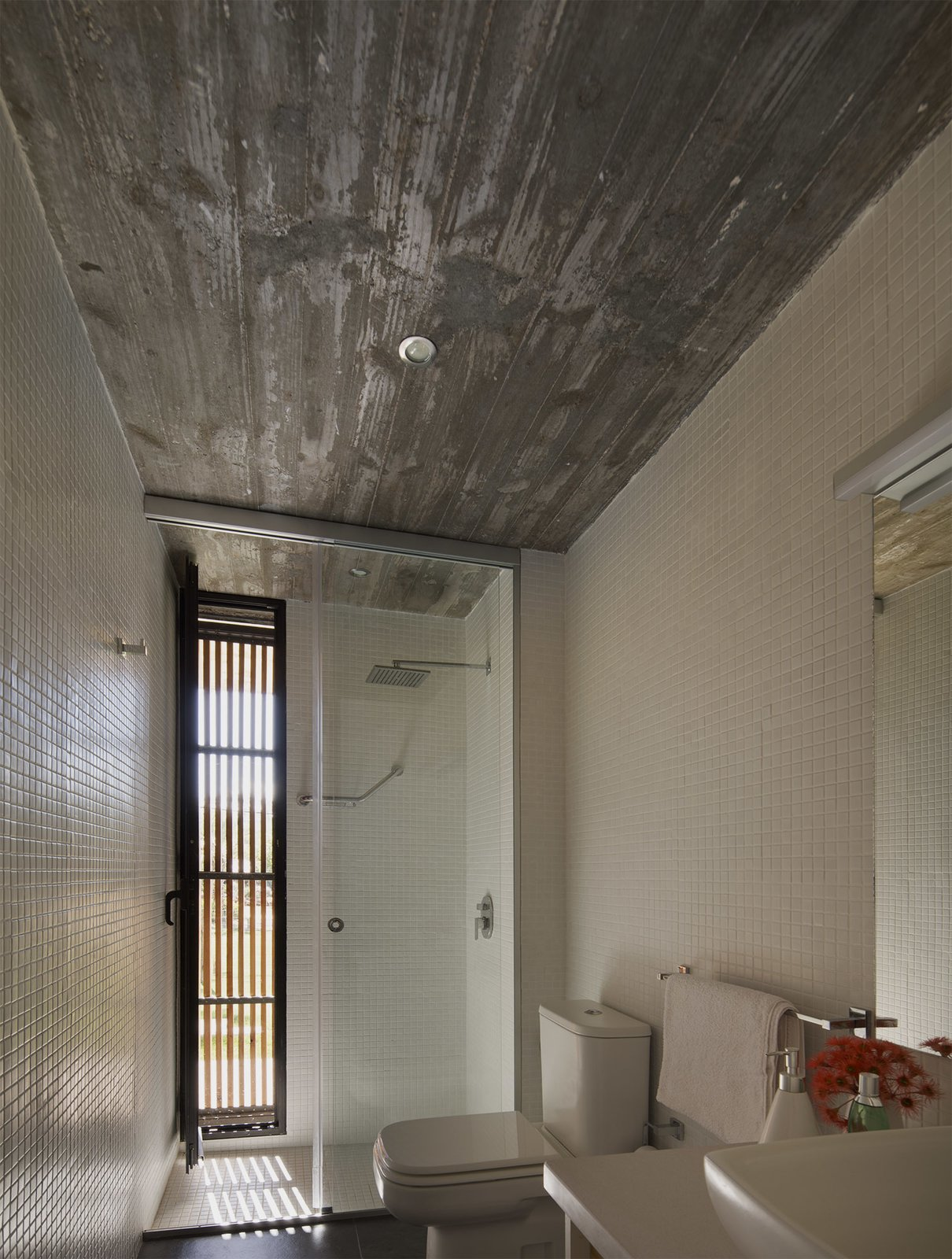 Bath Room, Concrete Floor, Corner Shower, Ceiling Lighting, Mosaic Tile Wall, and One Piece Toilet  MARINDIA HOUSE