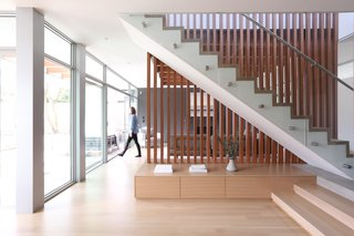 The two-level home displays a modest footprint to the surrounding neighborhood and is laid out on a simple open plan principle with the key day-to-day activity areas of kitchen, living and dining nestled around a dynamic open stair that uses wood verticals to carry the eye upwards to the second floor.