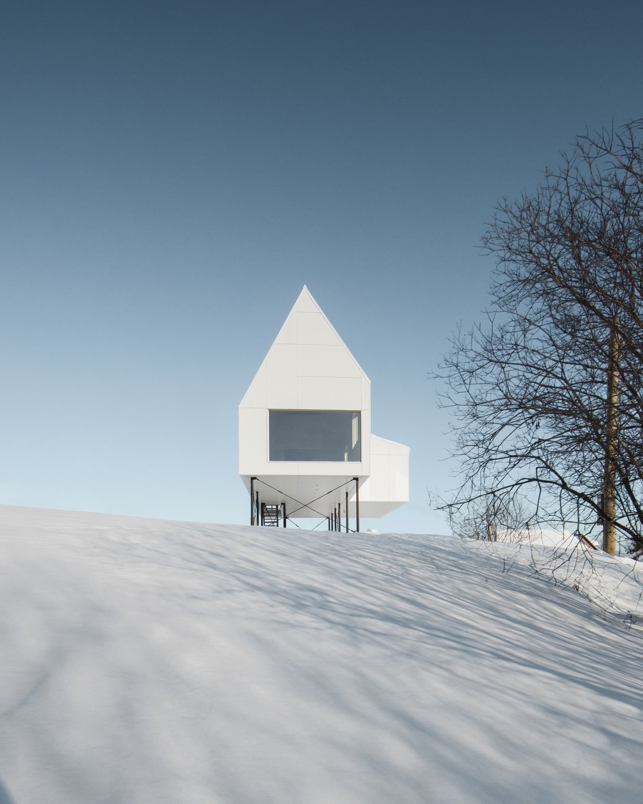 Exterior, Cabin Building Type, and Gable RoofLine  Photos from A Minimalist Winter Chalet Stands Tall on Stilts